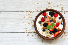 Bowl of greek yogurt with granola, oats, berries and nuts for healthy breakfast. Top view royalty free stock photo