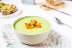 Bowl of Green peas cream soup with baked carrot and microgreen sprouts on the served white wooden table. Healthy food, vegitarian royalty free stock photos