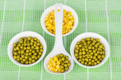 Bowl with green peas, sweet corn and plastic spoon Royalty Free Stock Images