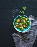 Bowl of green salad with avocado, arugula, cherry tomatoes and sunflower seeds, grilled bred slices, fresh herbs over Stock Photo