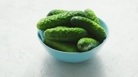 Bowl of green shiny cucumbers. Closeup of small bowl filled with shiny small green cucumbers in soft light on white background stock video footage