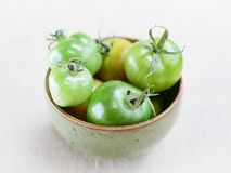 Bowl of green tomatoes stock image