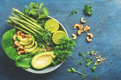 A bowl of green vegan salad with asparagus, avocado, lettuce, basil, mint, microgreen, lime and cashew nuts, blue rustic