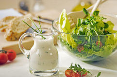 Bowl of greens and salad dressing. Bowl of greens and a jug of salad dressing Royalty Free Stock Image