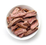 Bowl of grilled beef slices isolated on white, from above. Bowl of grilled beef slices isolated on white background, top view Royalty Free Stock Photography
