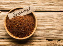 Bowl of ground coffee. Bowl full of ground coffee over an old wooden table Stock Photography