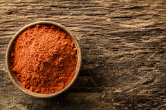 Bowl of ground red cayenne pepper. Overhead close up view of a bowl of ground red cayenne pepper on a weathered heavily textured wooden background with copyspace royalty free stock photos