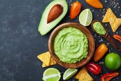 Bowl guacamole with avocado, lime and nachos top view. Mexican food. Bowl guacamole with avocado, green lime and nachos top view. Mexican food royalty free stock photo