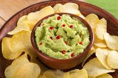 Bowl of guacamole dip and potato chips Royalty Free Stock Photos