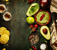 Bowl of guacamole with fresh ingredients and tequila shots. Bowl of Traditional latinamerican mexican sauce guacamole with fresh ingredients and tequila shots on Stock Image