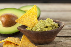 Bowl of Guacamole with nachos and avocados in background Stock Images