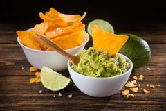 Bowl with guacamole sauce and nachos chips. On a wooden table royalty free stock photos