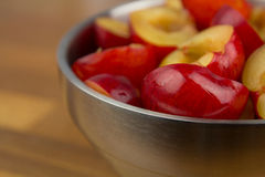 Bowl of halfed plums Stock Images