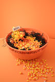 Bowl of Halloween Candy. Halloween arrangement featureing a large bowl of candy corn nestled in black raffia with a boo sign stock photo