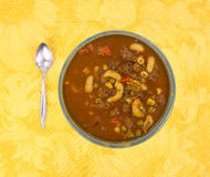 Bowl of hamburger soup with spoon on yellow tablecloth Stock Photo