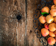 Bowl of harvested apricots.  Fresh apricots on wooden background Stock Image