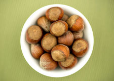 Bowl of hazelnuts against textured green background Stock Images