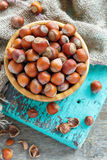 Bowl with hazelnuts on burlap and old green board. Stock Images