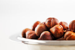 A bowl of hazelnuts on a white background Royalty Free Stock Photos
