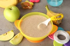 Bowl with healthy baby food. On gray table Royalty Free Stock Photo