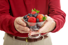 Bowl of Healthy Berries. Closeup of senior man's hands holding a bowl of healthy, antioxidant rich berries Stock Photography