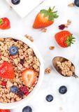 Bowl of healthy cereal granola with strawberries. And blueberries and glass of milk on marble board royalty free stock photos