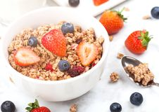 Bowl of healthy cereal granola with strawberries. And blueberries and glass of milk on marble board stock photos