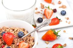 Bowl of healthy cereal granola with strawberries. And blueberries and glass of milk on marble board stock photography