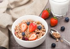 Bowl of healthy cereal granola with strawberries. And blueberries and glass of milk on wooden board stock photo