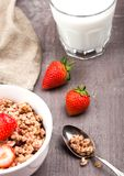 Bowl of healthy cereal granola with strawberries. And glass of milk on wooden board royalty free stock images