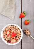 Bowl of healthy cereal granola with strawberries. And glass of milk on wooden board stock photo