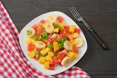 Bowl of healthy citrus fruit salad on dark wooden background. Top view. Royalty Free Stock Images
