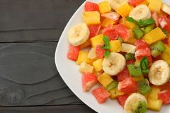 Bowl of healthy citrus fruit salad on dark wooden background. Top view. Royalty Free Stock Image