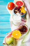 Bowl of healthy corn flakes breakfast cereal, milk and fruits on blue wood table Royalty Free Stock Photography