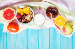 Bowl of healthy corn flakes breakfast cereal, milk and fruits on blue wood table Royalty Free Stock Image