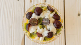 Bowl of healthy fresh fruit salad with cream. Close up fresh fruit salad with kiwi, grapes and banana wih cream in glass bowl top view Stock Images