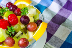 Bowl of healthy fresh fruit salad and milk on pattern of Thai hand made fabric background. Bowl of healthy fresh fruit salad and milk on pattern of Thai hand Royalty Free Stock Image
