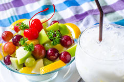 Bowl of healthy fresh fruit salad and milk on pattern of Thai hand made fabric background. Bowl of healthy fresh fruit salad and milk on pattern of  fabric Stock Photography