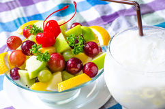 Bowl of healthy fresh fruit salad and milk on pattern of Thai hand made fabric background. Bowl of healthy fresh fruit salad and milk on pattern of Thai hand Royalty Free Stock Photography