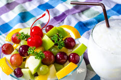 Bowl of healthy fresh fruit salad and milk on pattern of Thai hand made fabric background. Bowl of healthy fresh fruit salad and milk on pattern of Thai hand Royalty Free Stock Photo