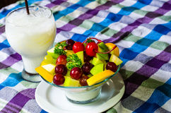 Bowl of healthy fresh fruit salad and milk on pattern of Thai hand made fabric background. Bowl of healthy fresh fruit salad and milk on pattern of Thai hand Royalty Free Stock Images