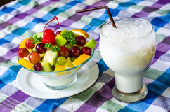 Bowl of healthy fresh fruit salad and milk on pattern of Thai hand made fabric background. Bowl of healthy fresh fruit salad and milk on pattern of Thai hand Stock Photos