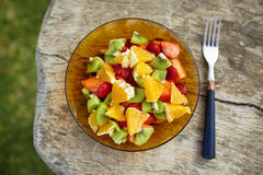 Bowl of healthy fresh fruit salad. With oranges, strawberries, kiwi and papaya on wooden background. Closeup top view royalty free stock photos
