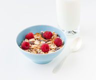 Bowl of healthy muesli with fresh raspberries. Bowl of healthy muesli  with fresh raspberries and a glass of milk. selective focus Royalty Free Stock Photo