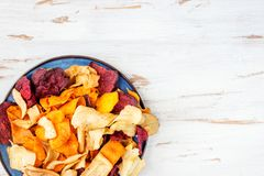 Bowl of Healthy Snack from Vegetable Chips, Crisps. Bowl of Healthy Snack from Vegetable Chips, such as Sweet Potato, Beetroot, Carrot, Parsnip on Light Wooden Royalty Free Stock Photo