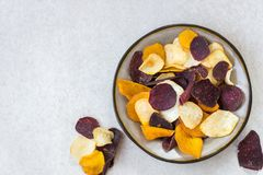 Bowl of Healthy Snack from Vegetable Chips, such as Sweet Potato. Beetroot, Carrot, Parsnip on Light Grey Background royalty free stock photography
