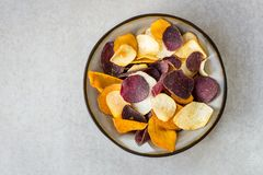 Bowl of Healthy Snack from Vegetable Chips, such as Sweet Potato. Beetroot, Carrot, Parsnip on Light Grey Background stock photos