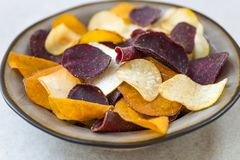 Bowl of Healthy Snack from Vegetable Chips, such as Sweet Potato. Beetroot, Carrot, Parsnip on Light Grey Background stock photo