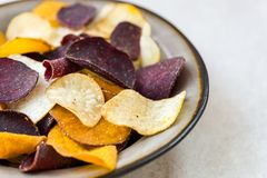 Bowl of Healthy Snack from Vegetable Chips, such as Sweet Potato. Beetroot, Carrot, Parsnip on Light Grey Background royalty free stock photos