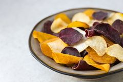 Bowl of Healthy Snack from Vegetable Chips, such as Sweet Potato. Beetroot, Carrot, Parsnip on Light Grey Background royalty free stock image